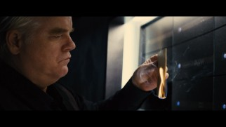 This deleted scene shows an envelope catching fire in the hands of Plutarch (Philip Seymour Hoffman).
