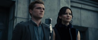 Peeta (Josh Hutcherson) and Katniss (Jennifer Lawrence) deliver solemn speeches at the districts of fallen young tributes.