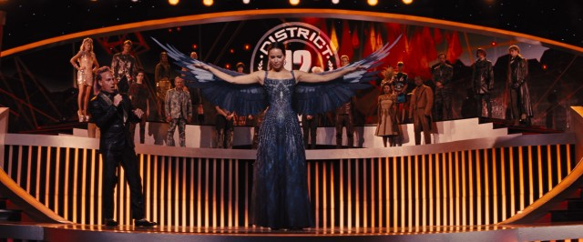 Katniss Everdeen (Jennifer Lawrence) wows Caesar Flickerman and his captive audience with her winged Mockingjay dress.