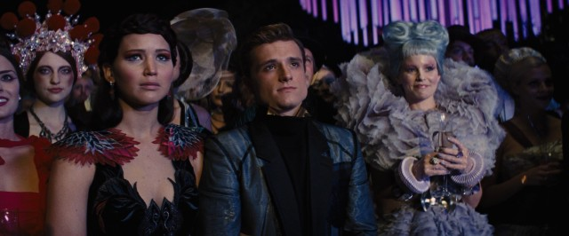 "Katniss (Jennifer Lawrence), Peeta (Josh Hutcherson), and Effie (Elizabeth Banks) are on hand for the opening ceremony of the third Quarter Quell Hunger Games in ""The Hunger Games: Catching Fire."""