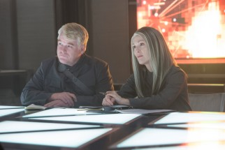 Having found their Mockingjay and agreed to her demands, Plutarch (Philip Seymour Hoffman) and President Coin (Julianne Moore) work on propaganda campaigns to strengthen their cause.