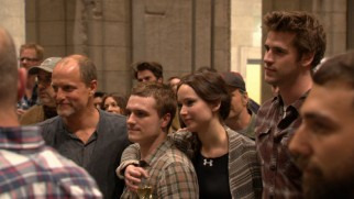 "Hunger Games core cast members Woody Harrelson, Josh Hutcherson, Jennifer Lawrence, and Liam Hemsworth are all ears during the series' wrap party toasts near the end of ""Pawn No More."""
