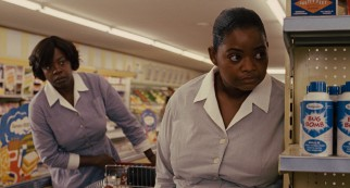 Aibileen (Viola Davis) and Minny (Octavia Spencer) are shocked to spot someone reading their book at the supermarket deli counter.