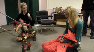 Teri Polo gets a demonstration of a creepy clown puppet.