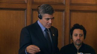 "George Clooney directs himself while co-writer/producer Grant Heslov looks on in ""Believe."""