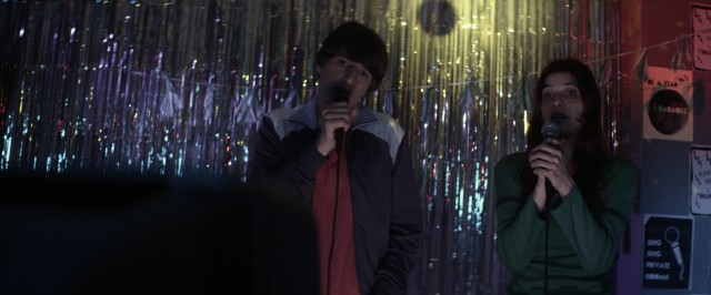 "Louis (Demetri Martin) and Carol (Lake Bell) sing karaoke together in ""In a World..."""