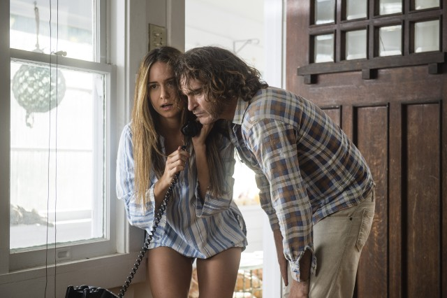 "Shasta (Katherine Waterston) and Doc (Joaquin Phoenix) take a phone call together in ""Inherent Vice."""