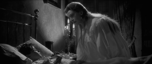 "Miss Giddens (Deborah Kerr) is troubled by the words and actions of Miles (Martin Stephens), one of two children to whom she is governess in ""The Innocents."""