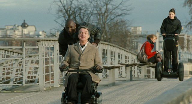 "Driss (Omar Sy) and Philippe (François Cluzet) enjoy a fast ride on Philippe's souped-up wheelchair in the 2011 French comedy ""The Intouchables."""