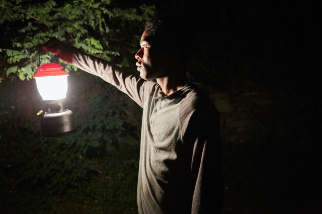 Seventeen-year-old Travis (Kevin Harrison Jr.) goes searching in the dark woods with a torch in hand.