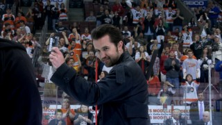 Mac (Rob McElhenney) relishes the chance to look cool while taking his center ice slap shot at a Flyers game.