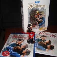 A photograph of the It's a Wonderful Life Gift Set contents: box, Blu-ray, booklet, and bell.