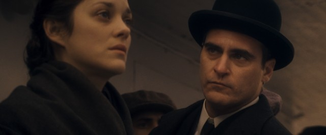 "Bruno Weiss (Joaquin Phoenix) has his eye caught by Ewa Cybulska (Marion Cotillard), but the feeling is not mutual in James Gray's ""The Immigrant."""
