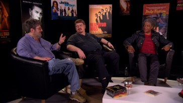 "Elvis Mitchell (right) and other film critics break down ""Jackie Brown"" in front of a semi-circle of Quentin Tarantino movie posters."