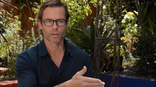 Guy Pearce dons glasses for his behind the scenes featurette interview.