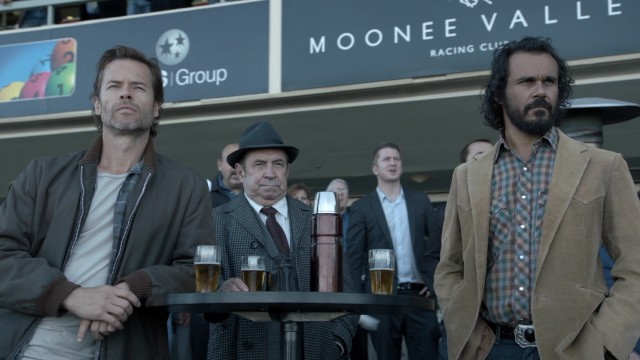 When he's not on the search for answers, Jack Irish (Guy Pearce) can be found at the racetrack with his mates Harry Strang (Roy Billing) and Cam Delray (Aaron Pedersen).