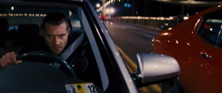 Charlie (Jai Courtney) and authorities pursues Jack Reacher in the obligatory car chase sequence.