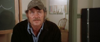 Quint (Robert Shaw) offers his expert shark hunting services for the hefty price of $10,000.