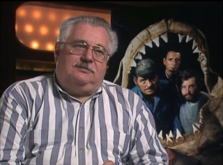 "Screenwriter and Jaws Log"" author Carl Gottlieb speaks in front of a promotional cast shot in 1995's two-hour laserdisc documentary ""The Making of 'Jaws.'"""