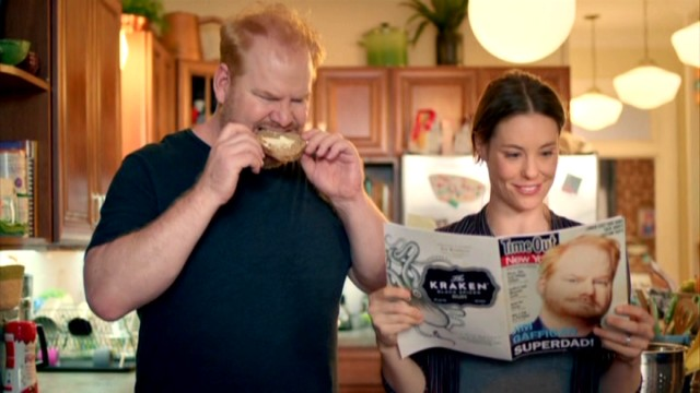 "While Jim Gaffigan bites into a bagel, his wife Jeannie (Ashley Williams) reads about the man Time Out New York calls ""Superdad!"""