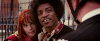 British police officers confront Kathy Echingham (Hayley Atwell) and her boyfriend Jimi Hendrix (André Benjamin) about his choice in military coats.
