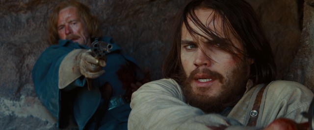 John Carter (Taylor Kitsch) and his commanding officer (Bryan Cranston) aim their weapons at retreating Apache.