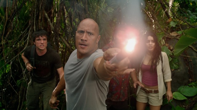 Hank (Dwayne Johnson) holds a lit flare at a giant lizard (and 3D viewers), a tactic Sean (Josh Hutcherson) declares unwise.