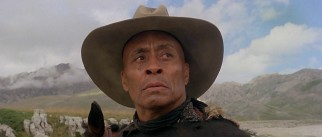 Though his glory days of archery, banjo, and hair are behind him, George (Woody Strode) still has a bit of fight left in him.