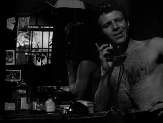 As a shirtless Davey (Jamie Smith) talks on the phone, nearby Gloria can be seen undressing in his mirror.