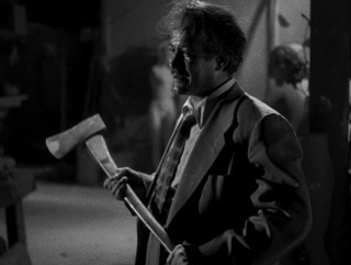 His hair a mess, Vinnie Rapallo (Frank Silvera) wields an axe in the climactic mannequin factory battle.