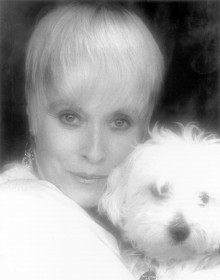 "Lisa Davis, the voice and reference model for Anita in ""101 Dalmatians"" appears alongside a dog in a current headshot."
