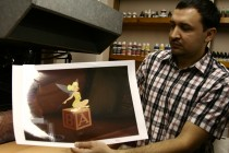 A Disney employee shows off a hand-made cel reproduction of Tinker Bell in the Ink and Paint building.