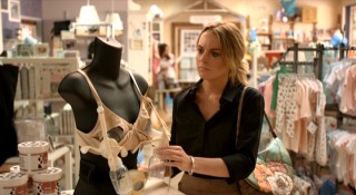 Thea (Lindsay Lohan) gets a hands-on look at a breast-milk-pumping contraption while browsing a maternity section.