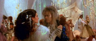 Sarah and Jareth share a dance in a glitzy '80s fantasy style ballroom sequence.