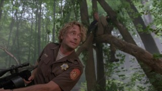 As Sheriff Riley, John Schneider uses his favorite, and only, expression and looks intently in the misty woods.