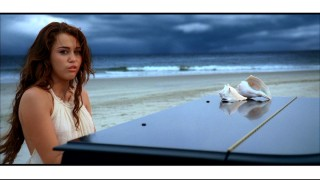 "As in the film, Miley Cyrus pouts and fakes piano playing in the ""When I Look at You"" music video."