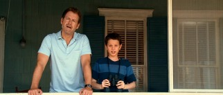 Father (Greg Kinnear) and son (Bobby Coleman) check out Ronnie's beach activities.