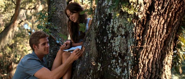 Will (Liam Hemsworth) and Ronnie (Miley Cyrus) carve initials in a tree as teenaged boys and girls do in the summer lovin' of Nicholas Sparks' mind.