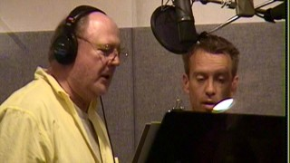 "Chris Sanders stands next to and directs David Ogden Stiers. The voice of Jumba (among many other Disney characters) is one of several Lilo & Stitch"" cast members featured in Disc 2's documentary."