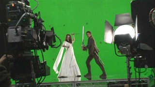 "Bridget Regan and Craig Horner pose for publicity shots in front of a green screen in ""Forging the Sword: Crafting a Legend."""