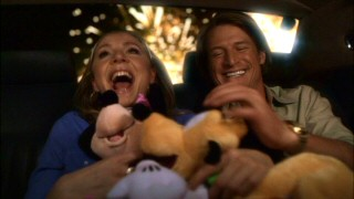 With fireworks going off behind them, Clarissa (Sarah Chalke) and Aaron (Philip Winchester) enjoy their newly-acquired Minnie Mouse and Pluto plush dolls. Little does she know he's got a whole room of plush dolls.