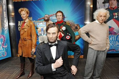 "Crystal the capuchin monkey holds up one of the ceremonial first DVD copies of ""Night at the Museum 2"" by the newly-unveiled wax statues of Abraham Lincoln, Amelia Earhart, Napoleon Bonaparte, and Albert Einstein."