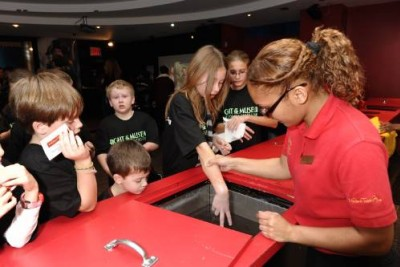 "Dressed in complimentary ""Night at the Museum: Battle of the Smithsonian"" T-shirts, young guests make wax molds of their hands with the assistance of a Madame Tussauds NY employee."