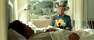 A bedridden Llewelyn wakes up to see Carson Welles (Woody Harrelson) bearing flowers.