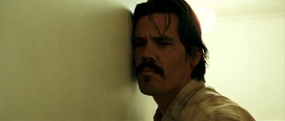 Llewelyn Moss (Josh Brolin) gives his motel wall a good listen.