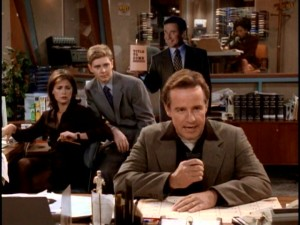 WNYX's cocky star reporter Bill McNeal (Phil Hartman) struggles to pen a worthy autobiography. Behind him, Lisa (Maura Tierney), Dave, and a cardboard Bill standee are among those expecting greatness.