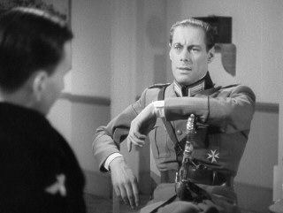 The monocle may seem a bit much, but Gus Bennett a.k.a. Dicky Randall (Rex Harrison) has no trouble convincing people that he's high-ranking Nazi official Ulrich Herzoff.
