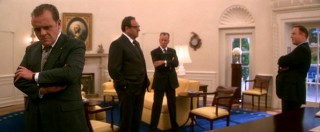 During a White House meeting, Nixon stands at a distance from three of his advisors (Sorvino, Woods, and J.T. Walsh).
