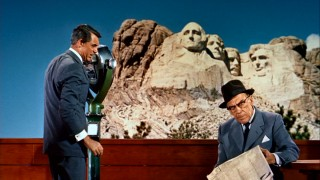 Roger Thornhill (Cary Grant) takes a break from binocularly looking at Mount Rushmore to ask The Professor (Leo G. Carroll) one of the many questions coming to mind.