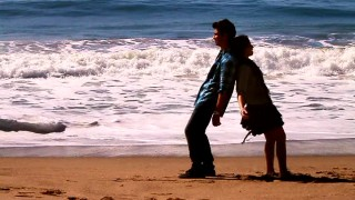 "Joe Jonas and Demi Lovato lean back on each other in their ""Make a Wave"" beach music video. I guess he's taller."
